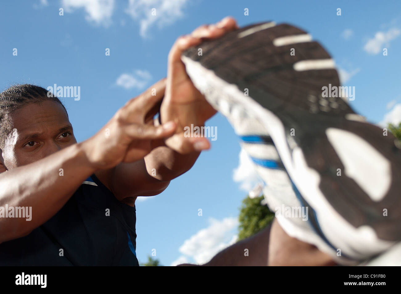 Close up of athlete stretching outdoors - Stock Image