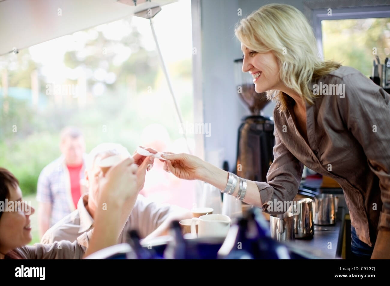 Woman serving coffee in food cart - Stock Image
