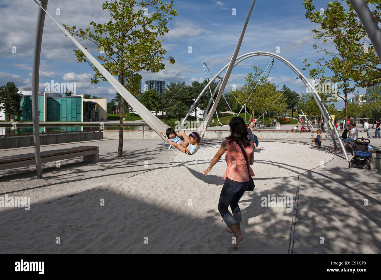 Children in a swing, playground at the Volkswagen Autostadt park, Wolfsburg, Lower Saxony, Germany - Stock Image
