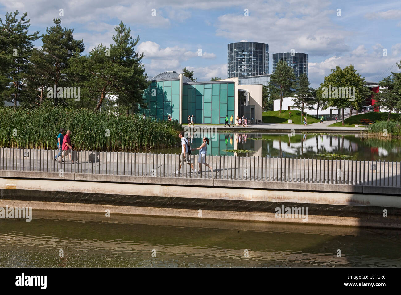 Visitors walking in the park in the Volkswagen Autostadt, Wolfsburg, Lower Saxony, Germany - Stock Image
