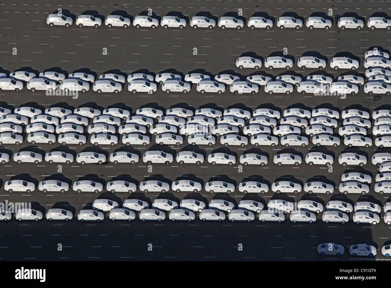 Aerial view of new vehicles waiting to be loaded at Emden harbour, Emden, lower Saxony, northern Germany - Stock Image