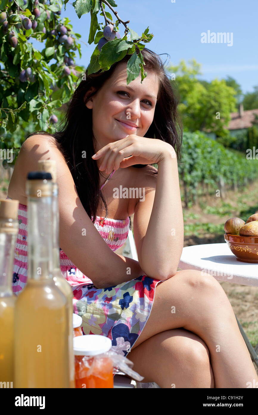 Smiling woman picnicking outdoors - Stock Image