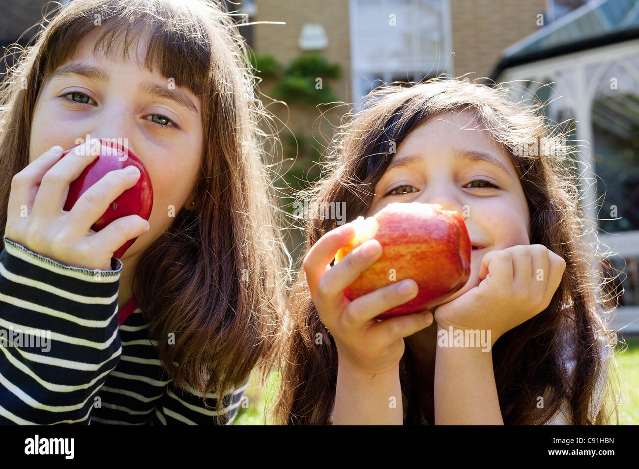 Girls eating apples outdoors - Stock Image