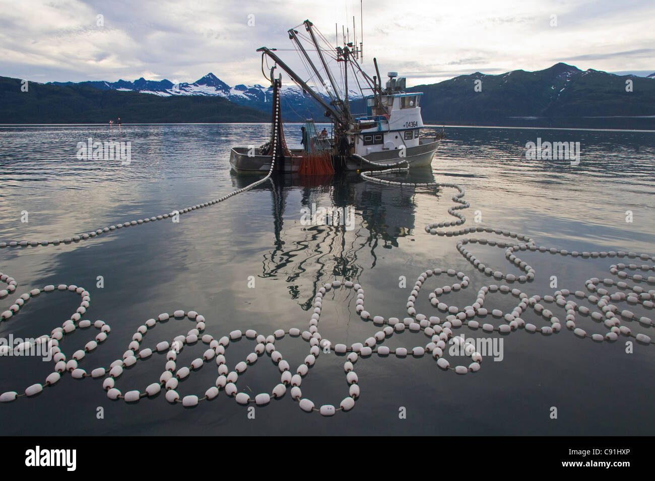 Pink salmon seiner beginning to haul net, Unakwik, Prince William Sound, Southcentral Alaska, Summer - Stock Image