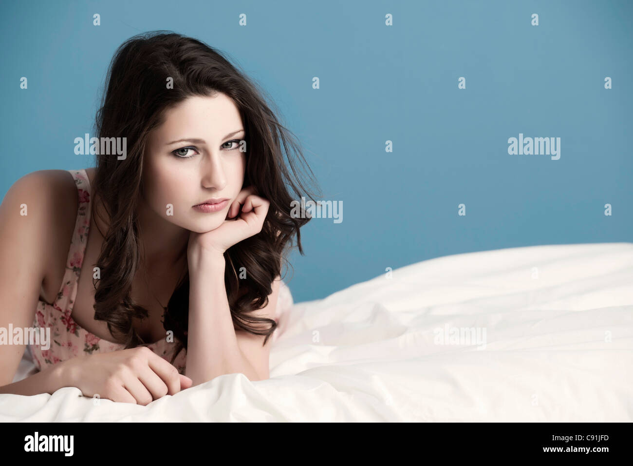 Teenage girl laying on bed - Stock Image