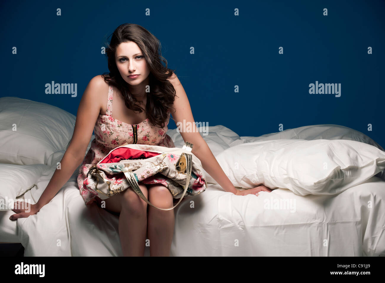 Teenage girl holding purse on bed - Stock Image