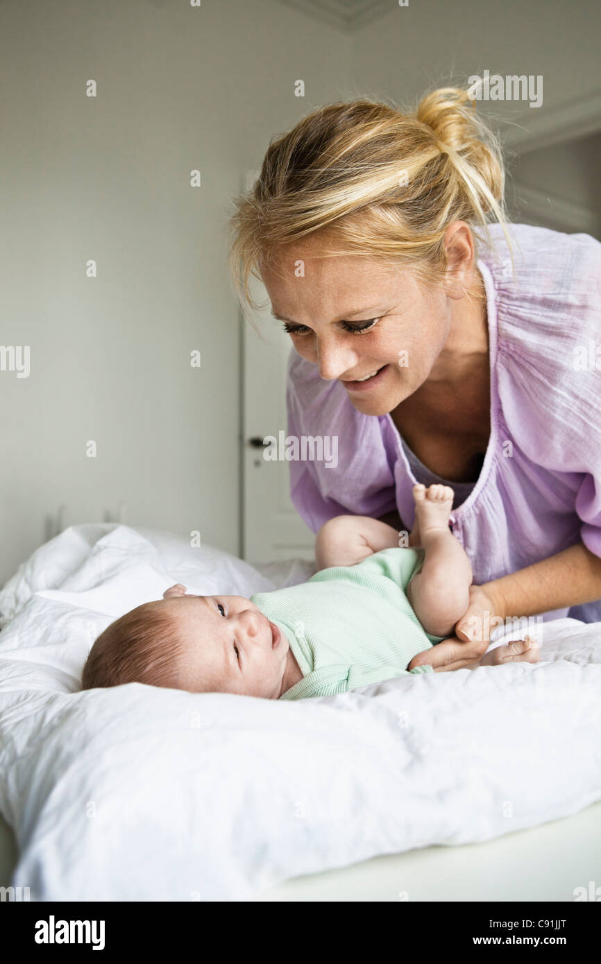 Mother changing infant's diaper - Stock Image