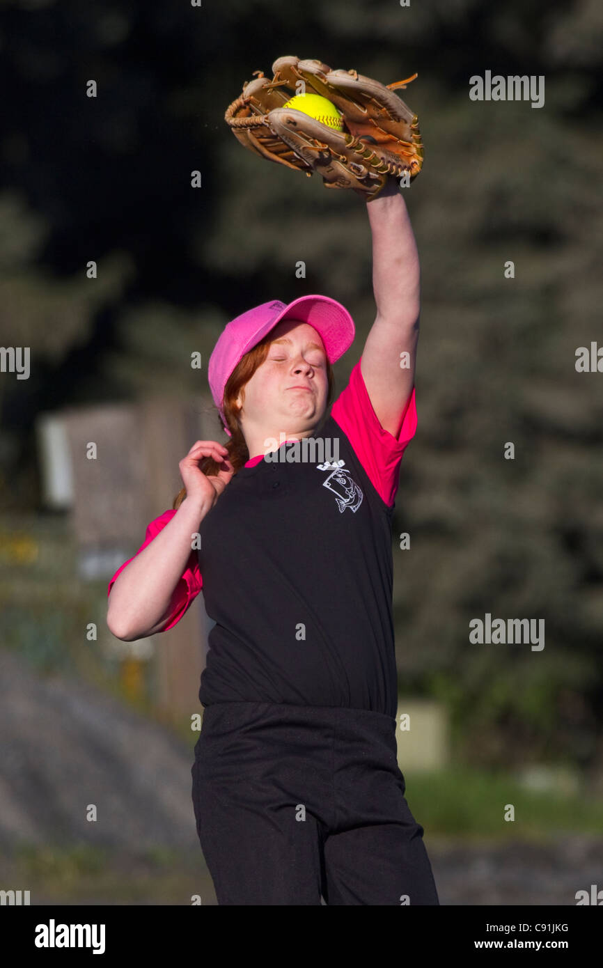 Young girl catching softball with eyes closed, Cordova little league, Cordova, Southcentral Alaska, Summer - Stock Image