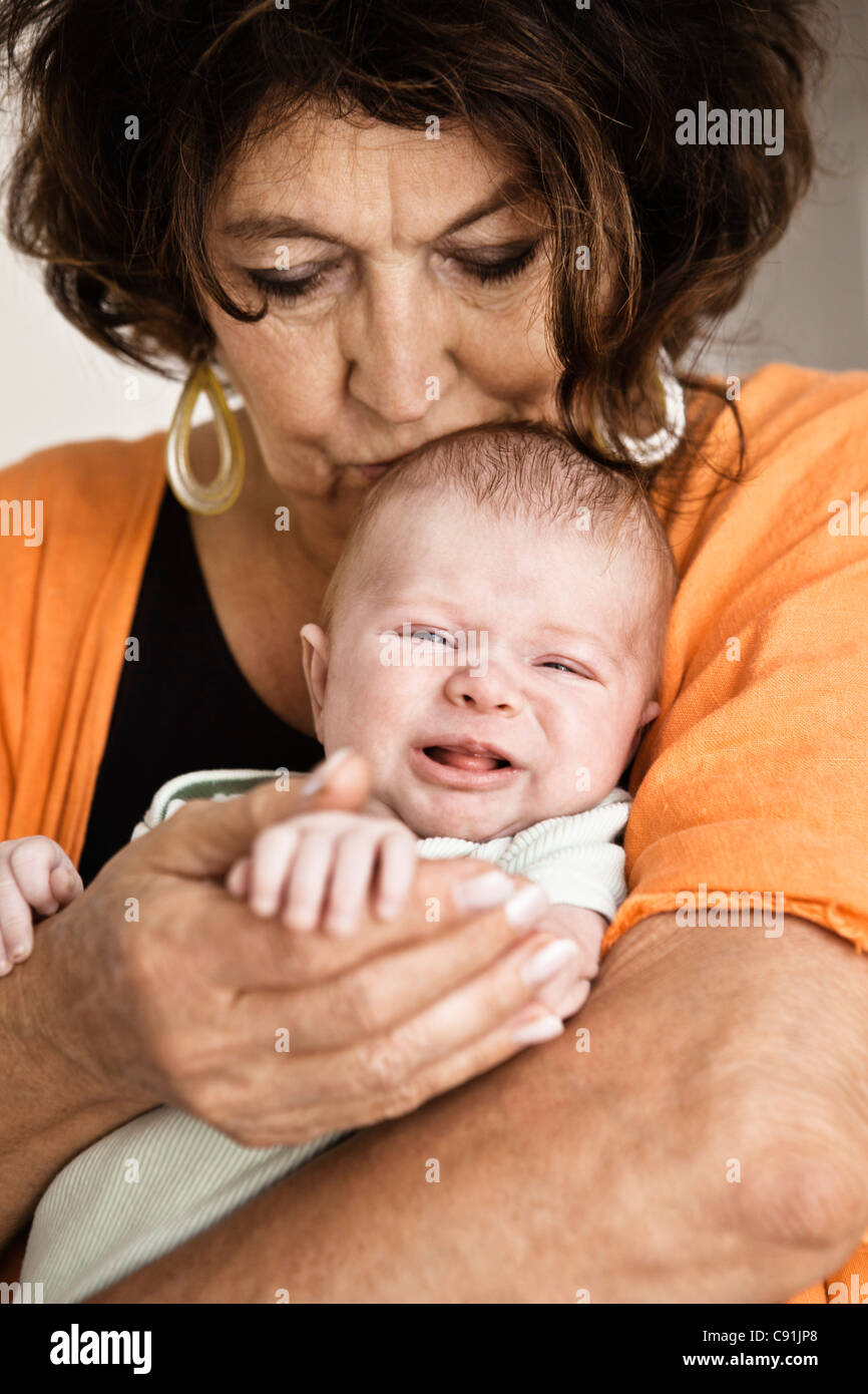 Grandmother cradling crying infant - Stock Image