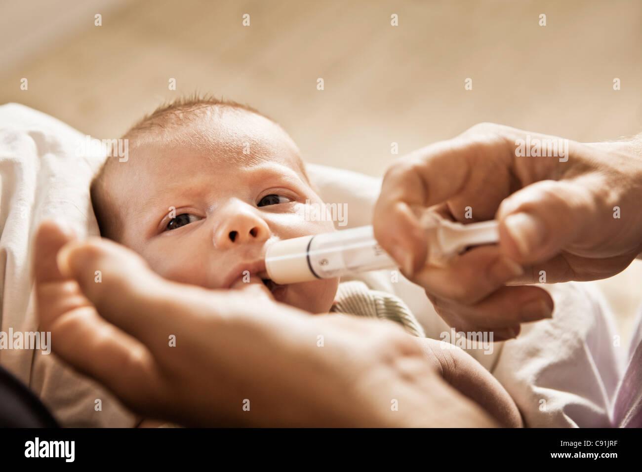 Parent feeding infant with syringe - Stock Image