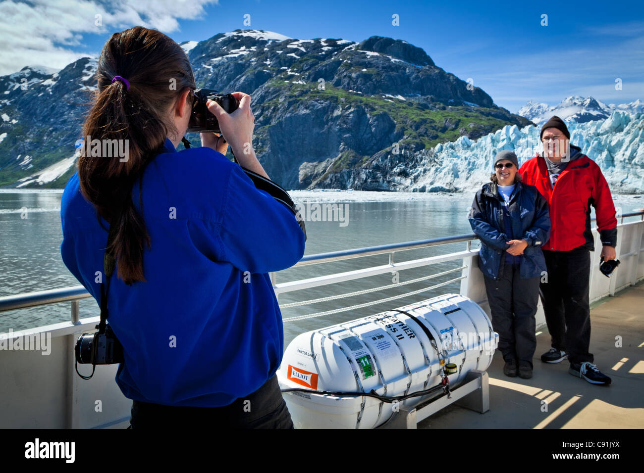A boat crew member on a tour boat taking pictures of a couple in front of Margerie Glacier, Glacier Bay National Stock Photo