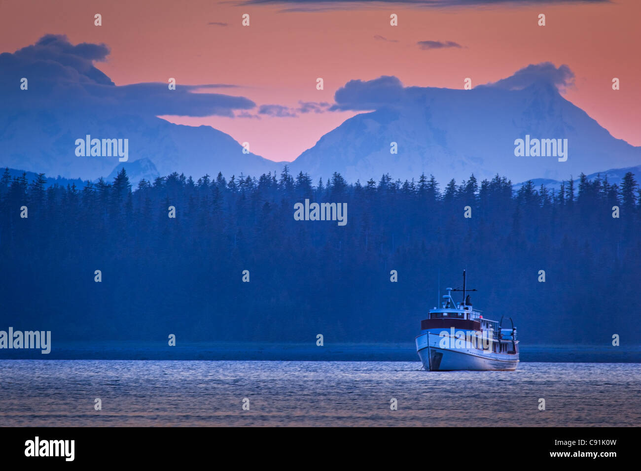 A boat sailing in Bartlett Cove at sunset with Fairweather Range in the background, Glacier Bay National Park & - Stock Image