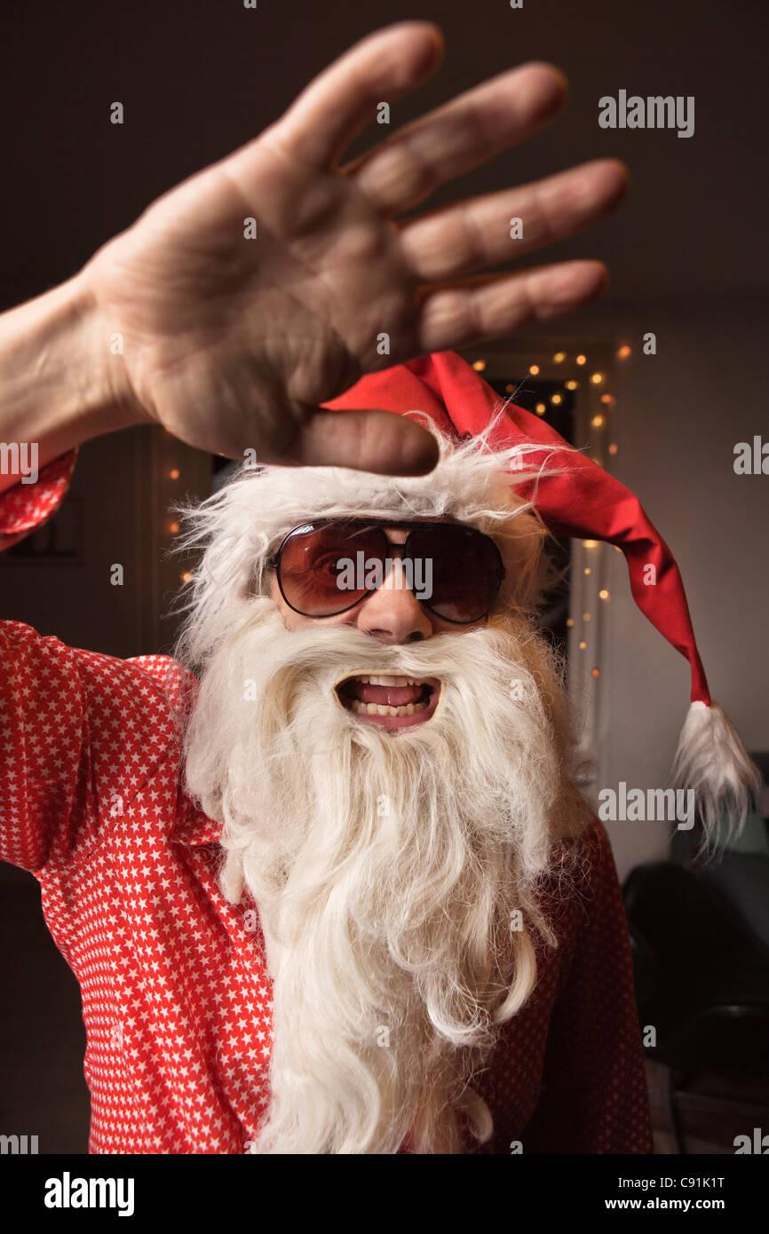 Man wearing Santa Claus hat and beard - Stock Image