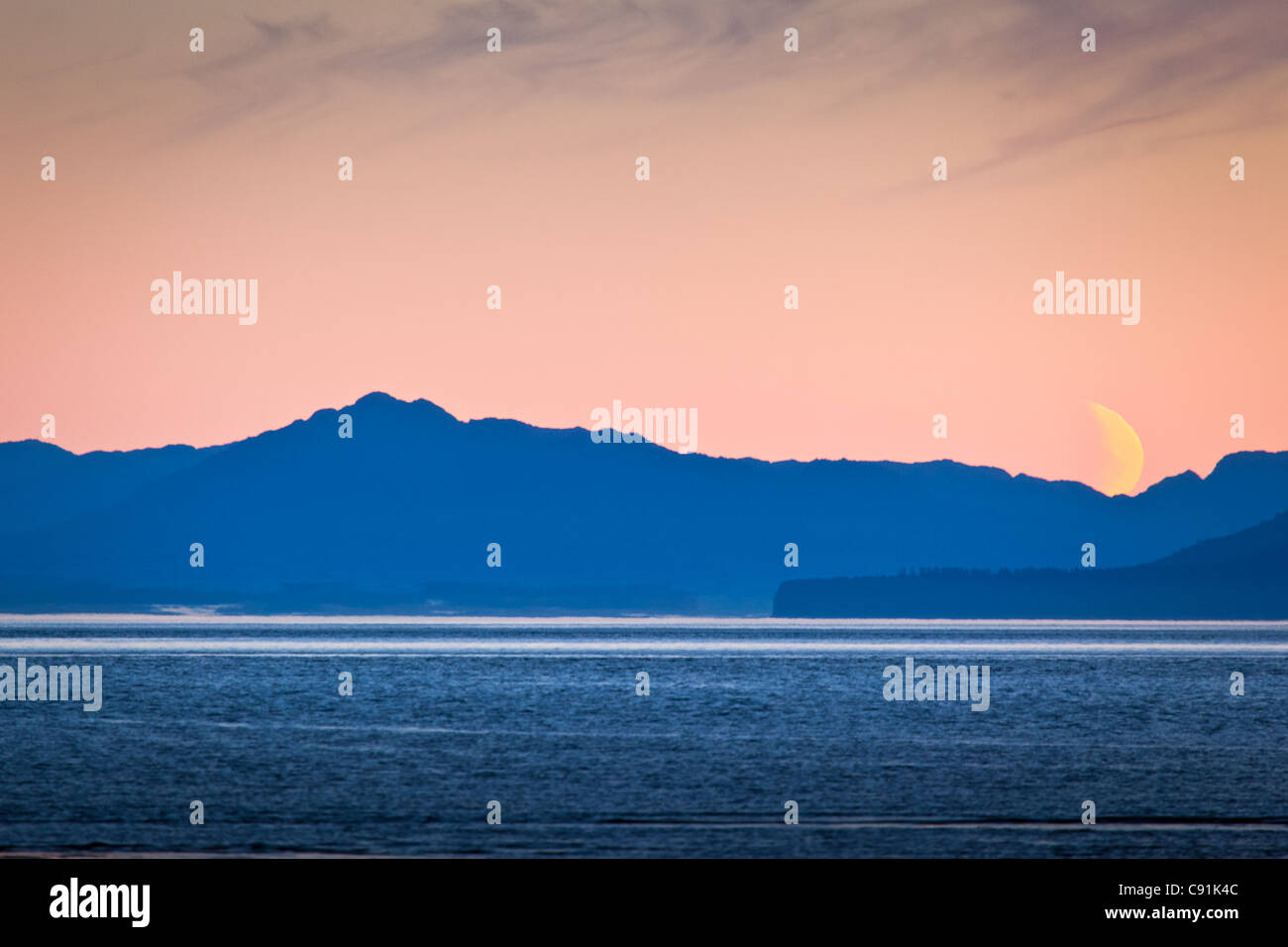 Scenic view at dawn of a crescent moon setting behind coastal mountains, Icy Strait, Glacier Bay National Park , - Stock Image