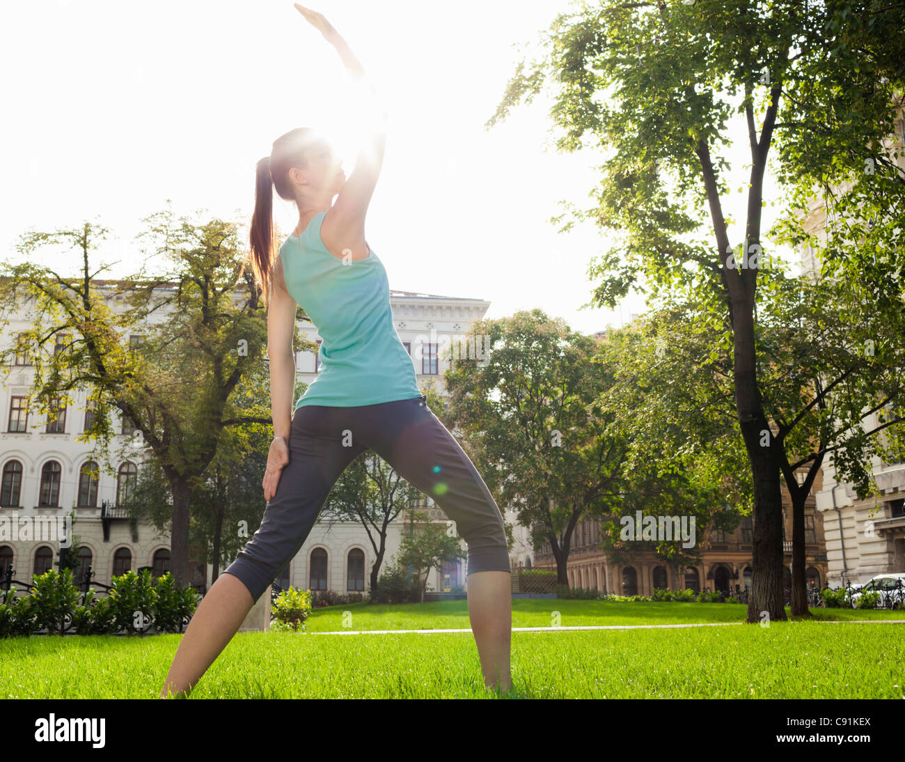 Woman stretching in urban park Stock Photo