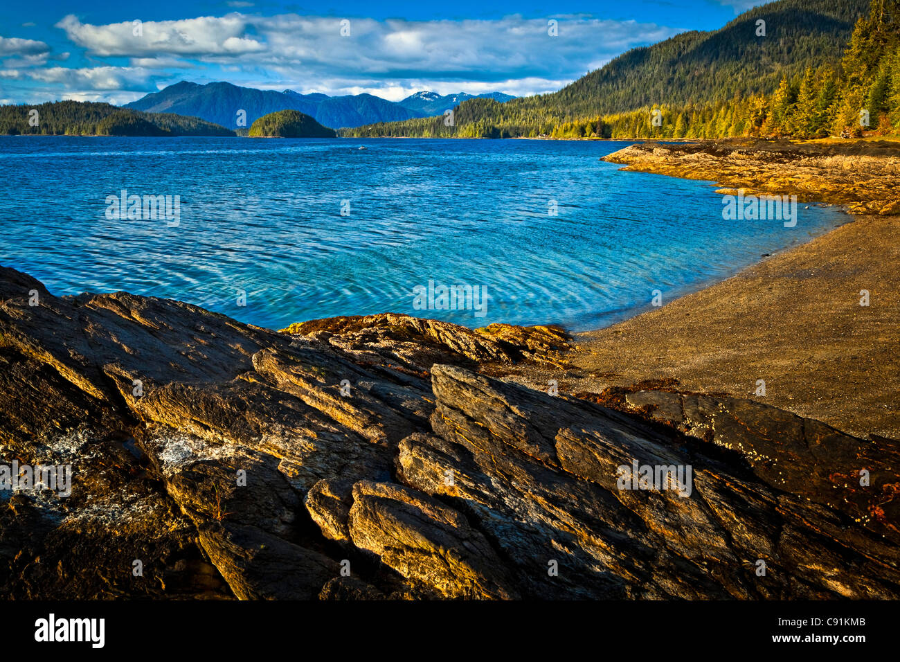 Sunlit rocks line the blue waters of Settler's Cove,  Settler's Cove State Recreation Site, Ketchikan, Southeast Stock Photo