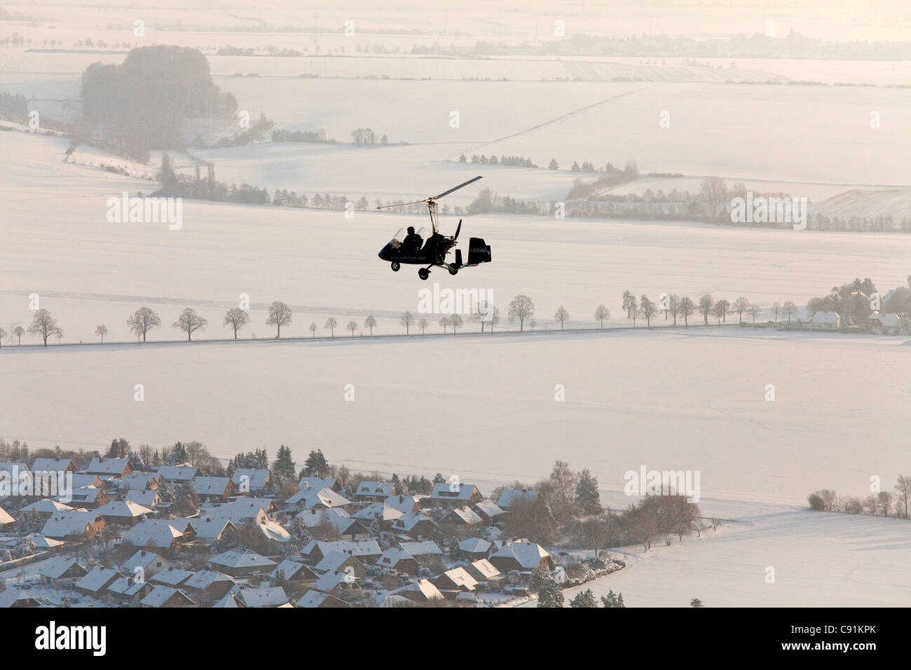 Aerial view of a two-seater autogyro, gyrocopter above a winter landscape, Lower Saxony, Germany - Stock Image