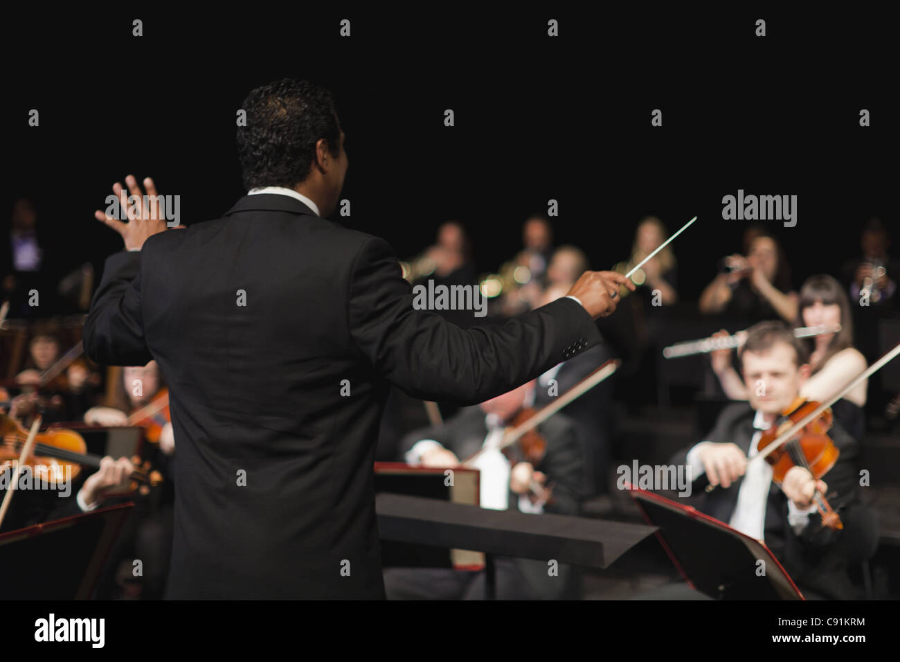 Conductor waving baton over orchestra - Stock Image