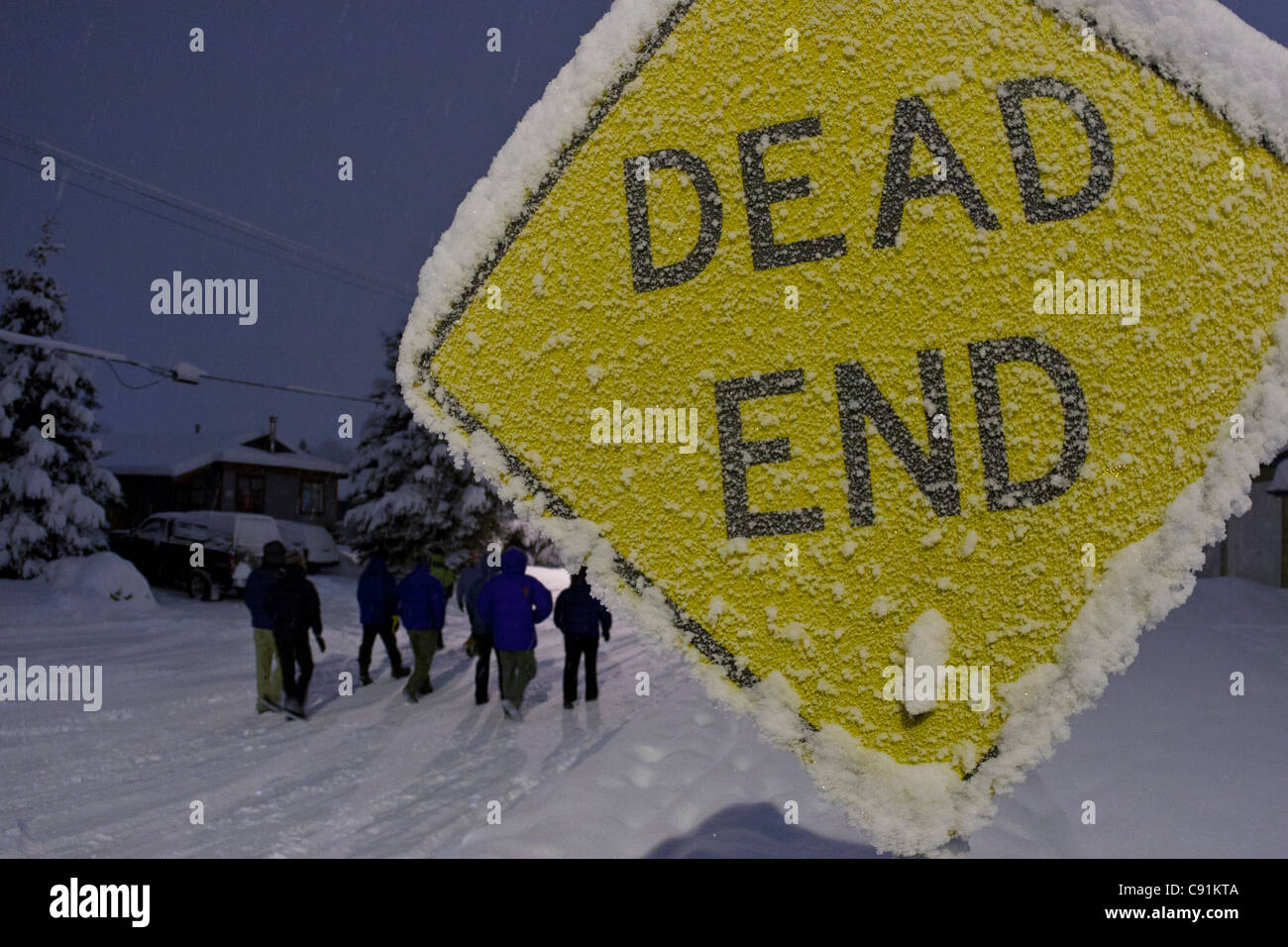 Group of people walk past a snowcovered and frosty Dead End road sign in a residential neighborhood, Anchorage, - Stock Image