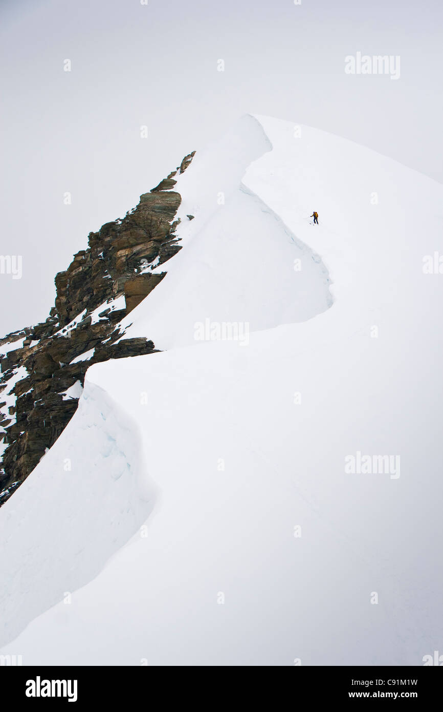 Skier ascends the north ridge of Mount Chamberlin in the Brooks Range, ANWR, Summer in Arctic Alaska - Stock Image