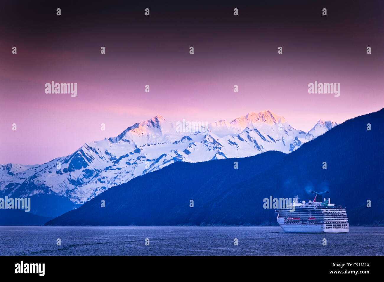 Carnival Cruise Spirit sailing through Lynn Canal at sunset, near Haines, Inside Passage, Southeast Alaska, Summer - Stock Image