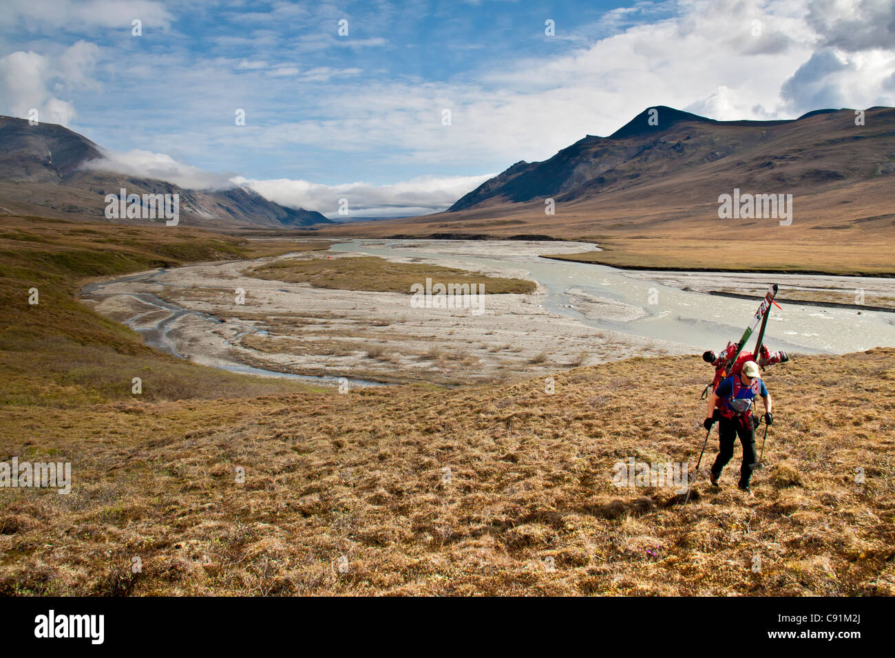 Backpacker carrying skis above the Hulahula River on the approach to Mount Chamberlin, Brooks Range, ANWR, Arctic - Stock Image