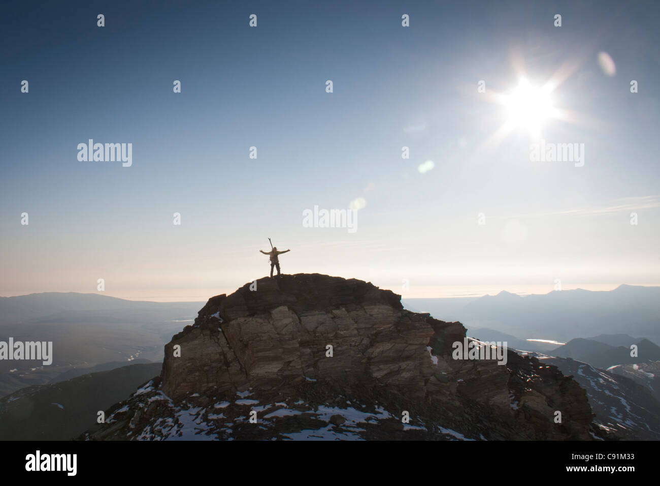 Hiker silhouetted against the Arctic Coastal plane on the north ridge of Mount Chamberlin, Brooks Range, ANWR in - Stock Image