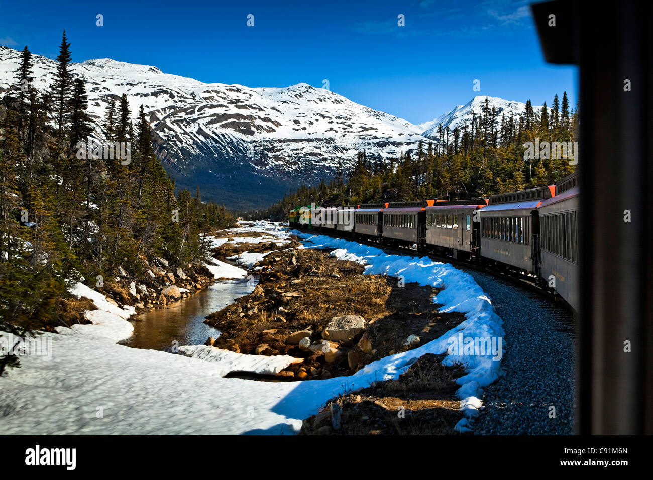 White Pass & Yukon Railroad on an early Summer excursion with snow still on the ground, Skagway, Southeast Alaska - Stock Image