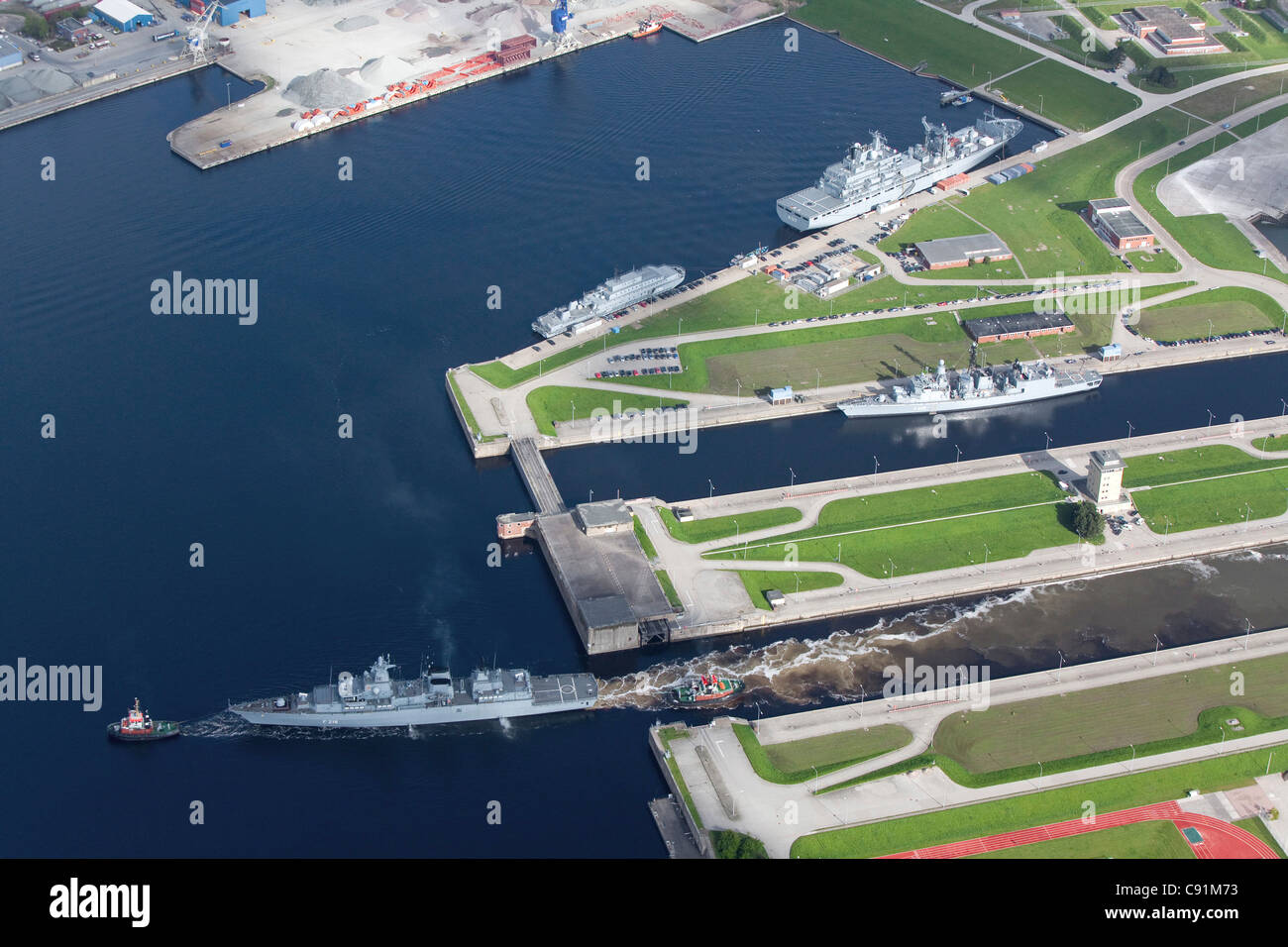 Aerial of tug boat towing battleship out of loch, naval harbour at Wilhelmshaven, Lower Saxony, Germany - Stock Image