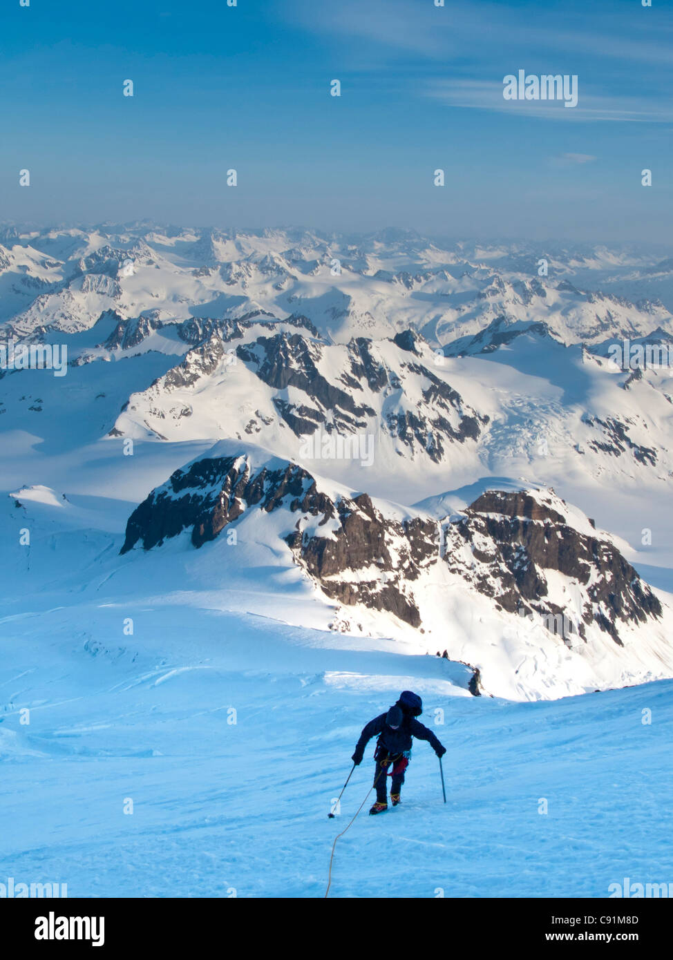 Climber leaning into high winds on northwest ridge of Mount Iliamna above Tongue Glacier and Chigmit Mountains, - Stock Image