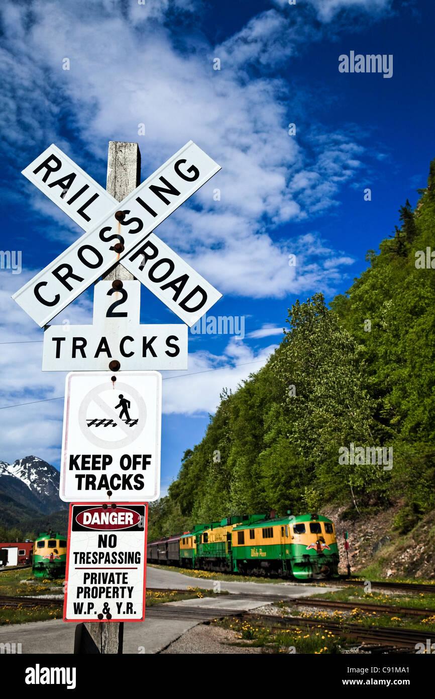 White Pass & Yukon Route Railway Train at a railroad crossing, Skagway, Southeast Alaska, Summer - Stock Image