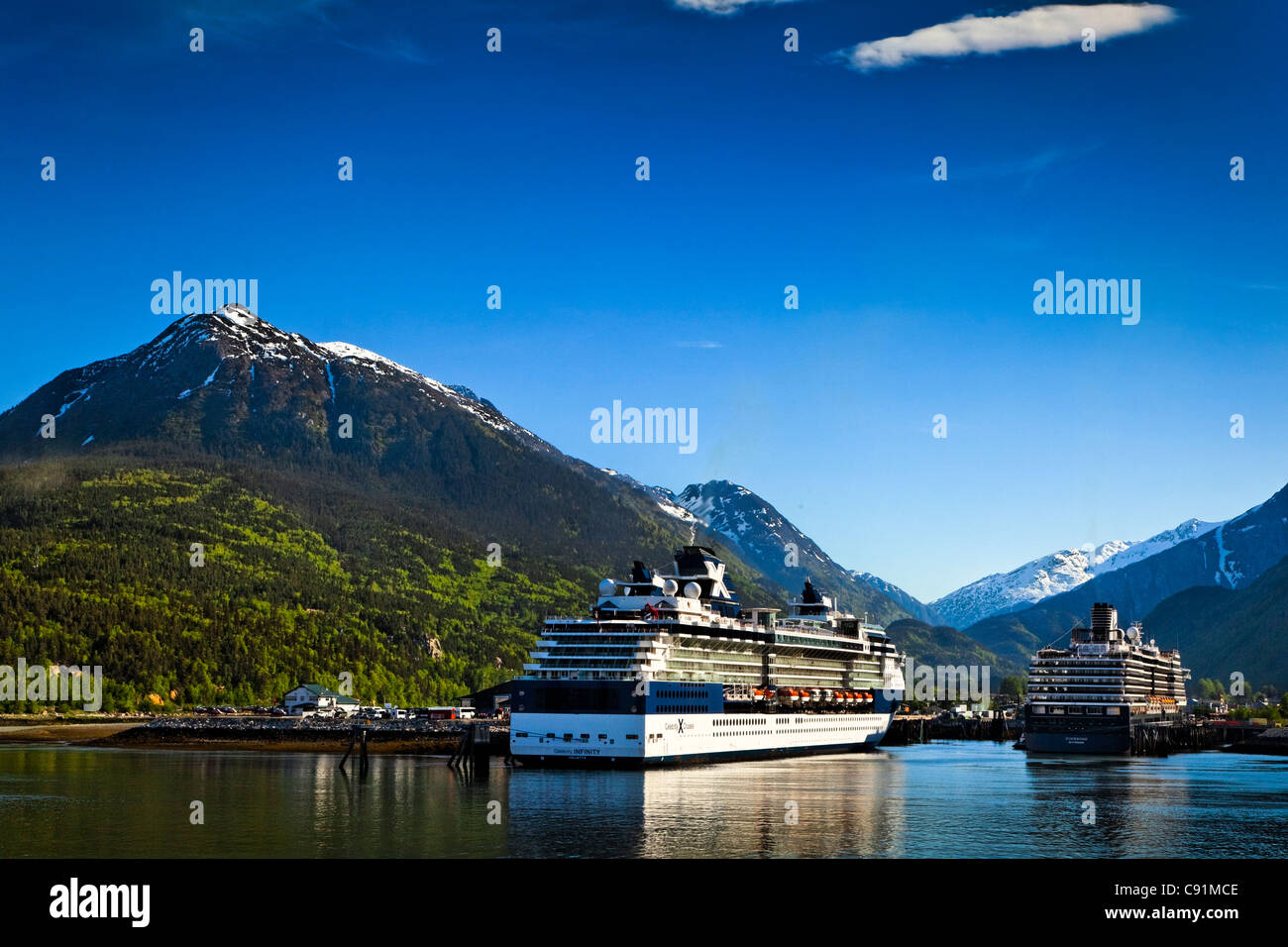 Alaska Marine Highway ferry moored next to a Celebrity Cruises cruise ship at the port of Skagway, Southeast Alaska, - Stock Image