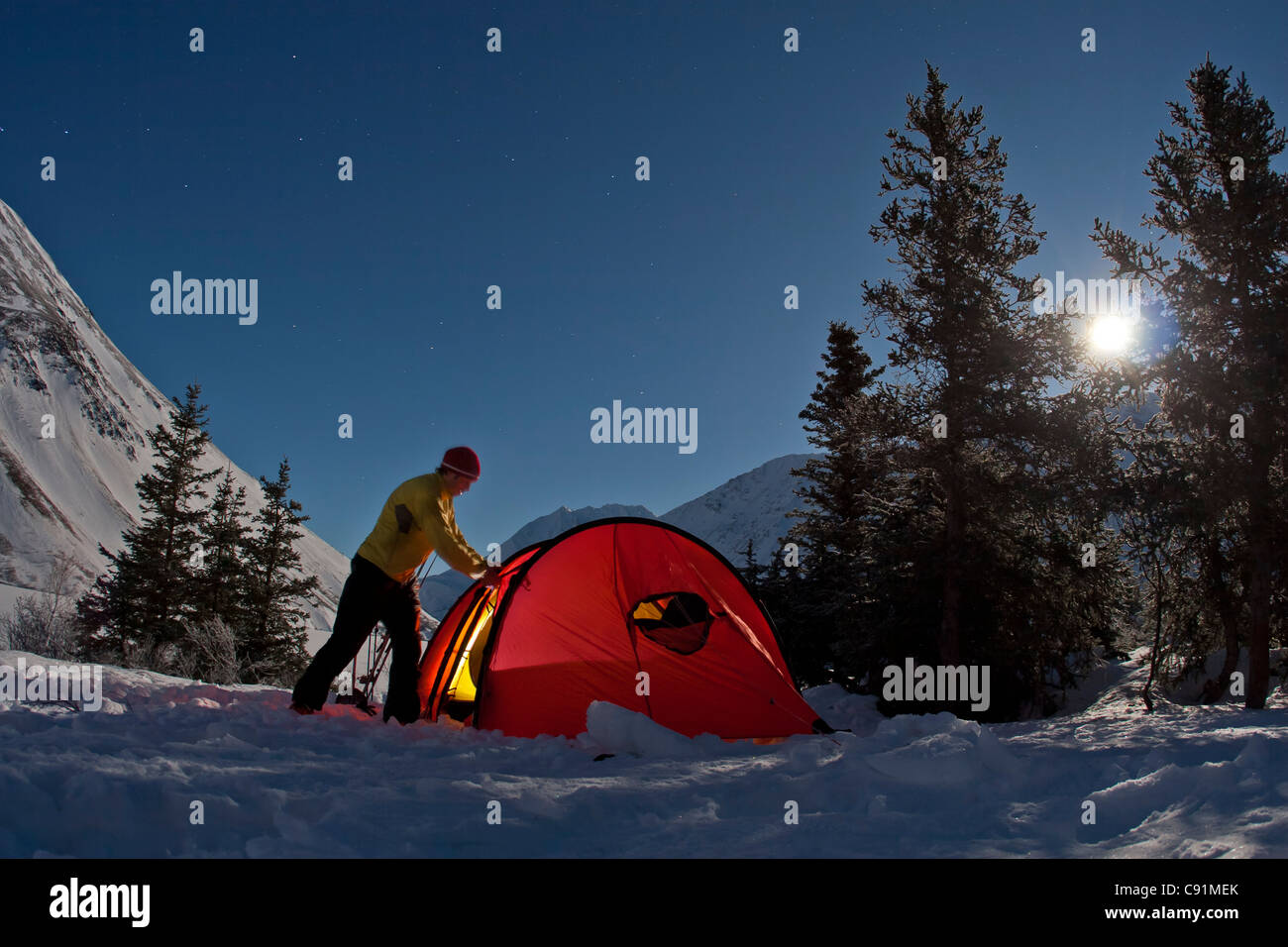 Camper setting up the tent under full moon light at the Crescent Saddle Cabin, Kenai Mountains, Kenai Peninsula, - Stock Image