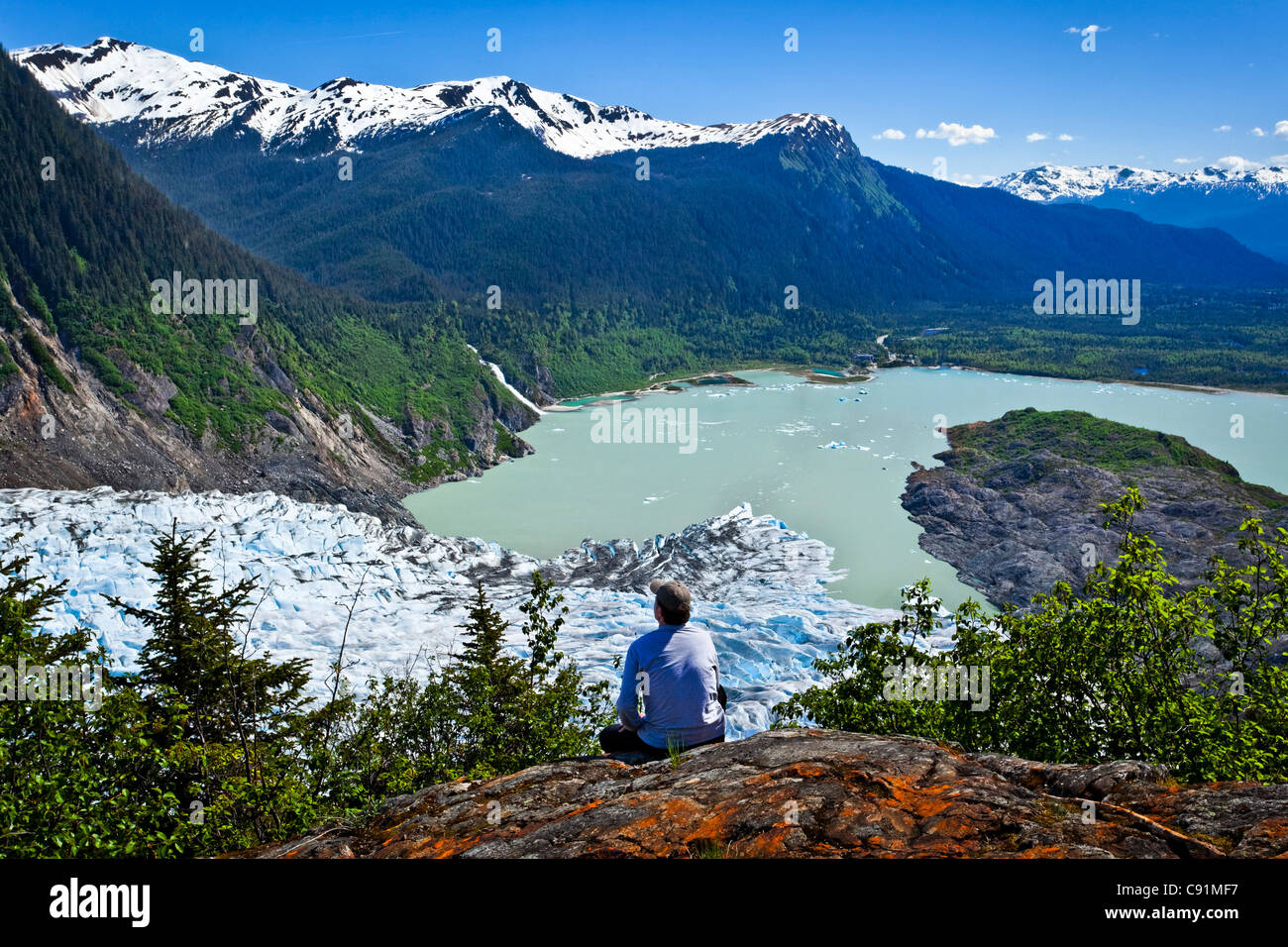 A male hiker looking down onto Mendenhall Glacier and Mendenhall Lake from West Glacier Trail, Juneau, Southeast - Stock Image
