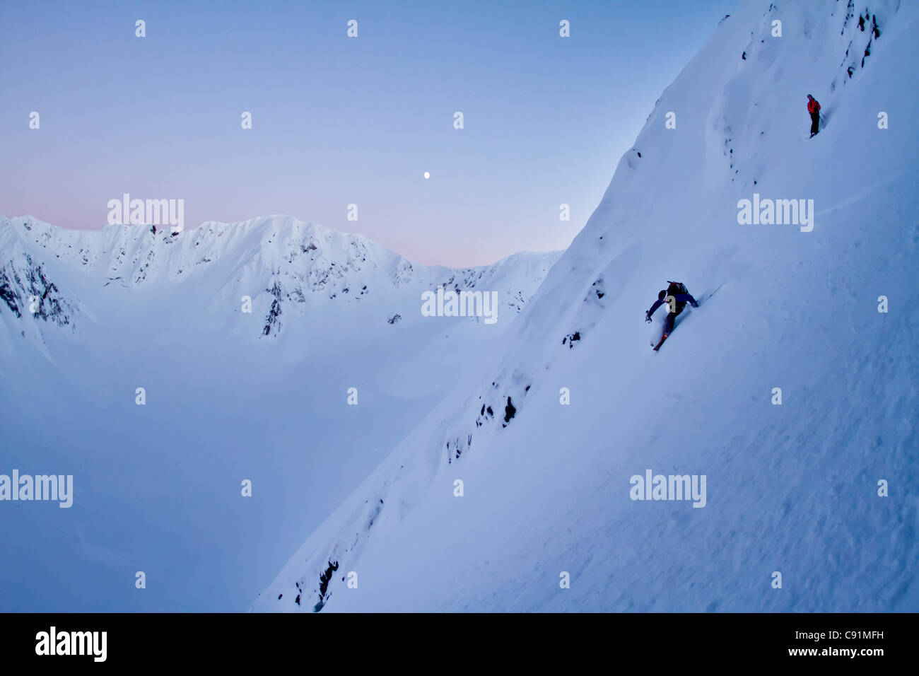 Skier and his spotter skiing steep powder on the north side of Kickstep Mountain, Turnagain Pass, Kenai Mountains, - Stock Image