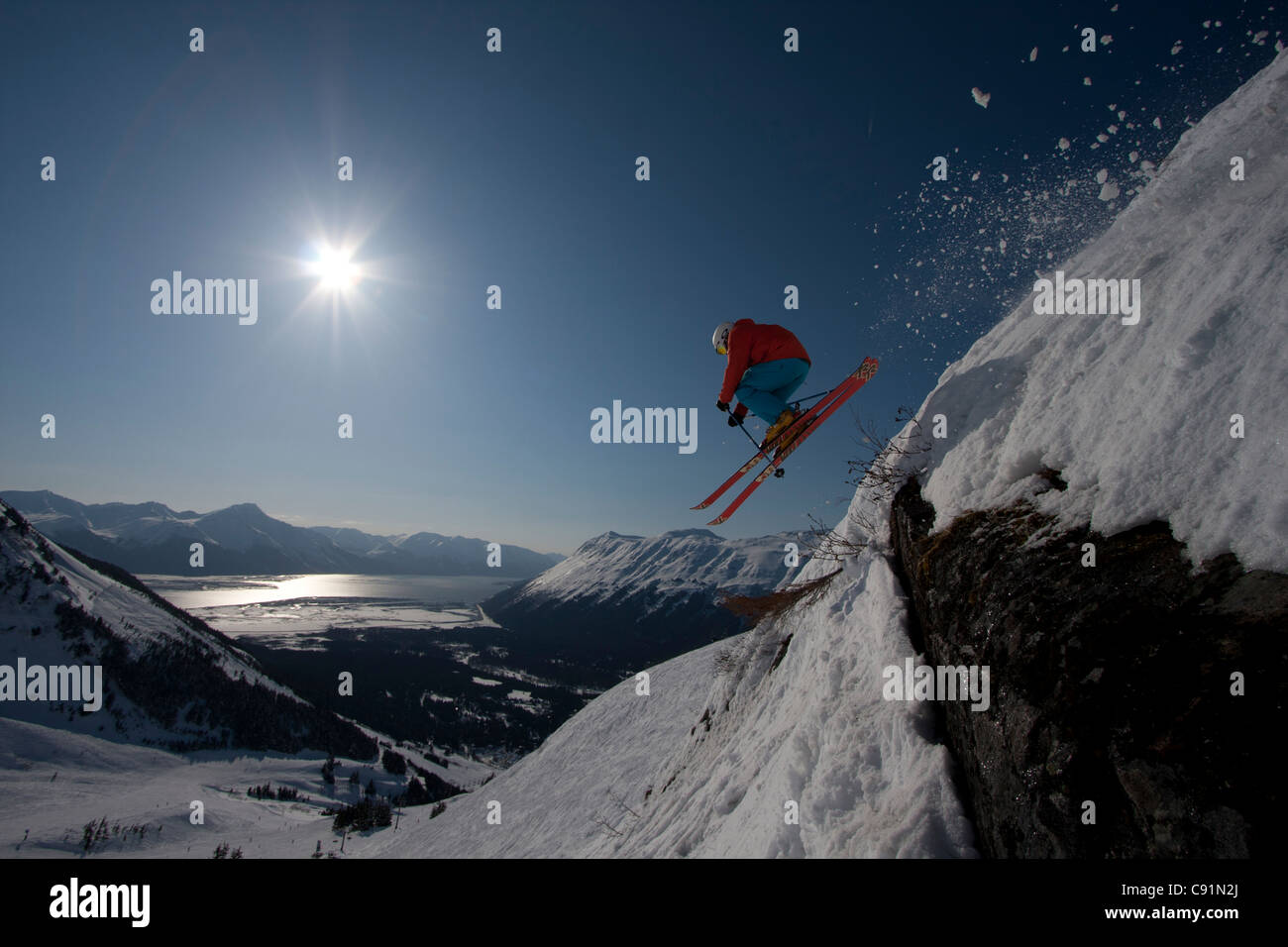 Silhouette of a downhill skier makes an extreme jump from a ledge while skiing at Alyeska Resort, Southcentral Alaska, - Stock Image