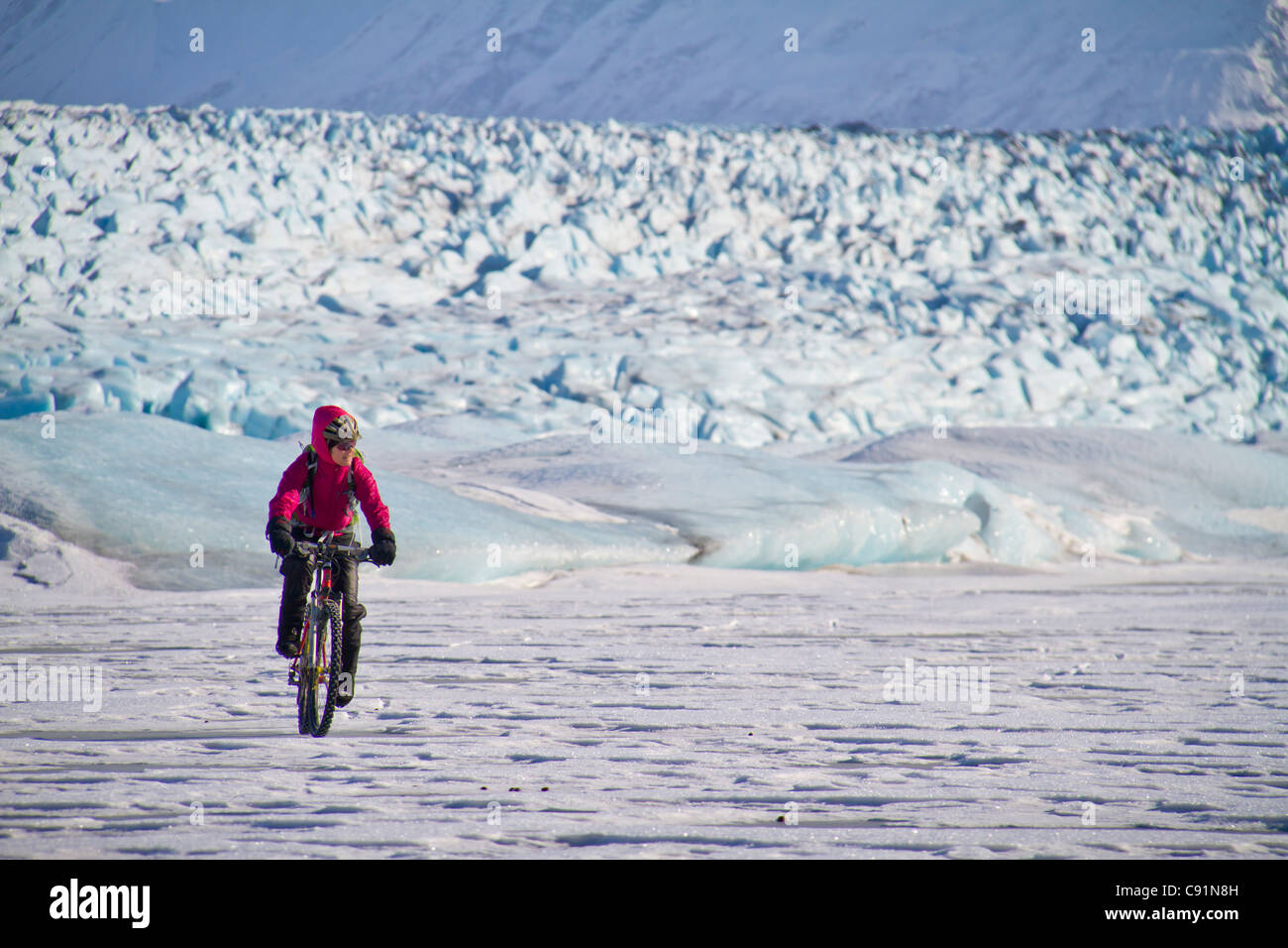 Woman Fat Tire mountain biking on the Knik Glacier, Chugach Mountains, Southcentral Alaska, Winter - Stock Image
