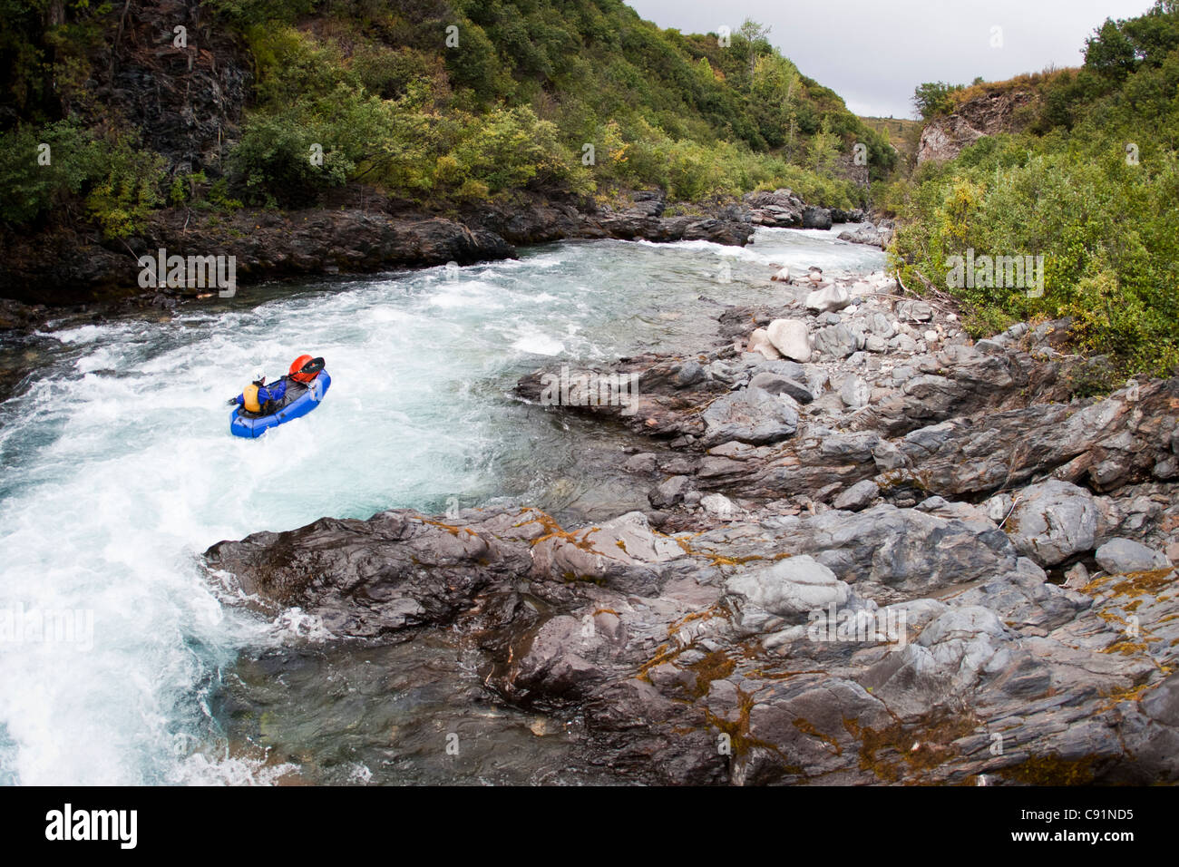 Woman packrafting whitewater on the East Fork of the Chulitna River, Alaska Range, Interior Alaska, Summer - Stock Image