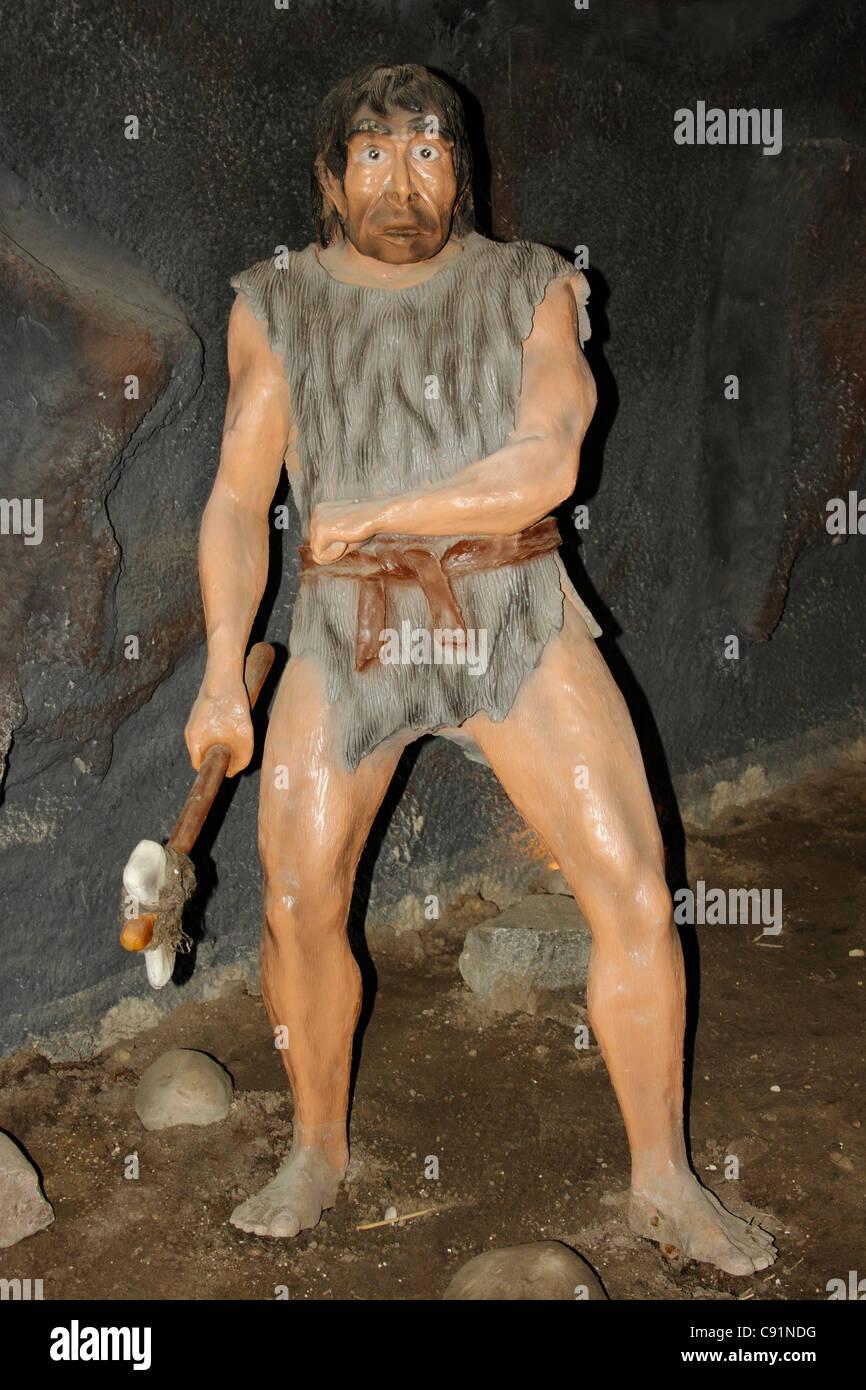 Homo neanderthalensis in a cave, Leba Park (prehistoric theme park), Poland - Stock Image