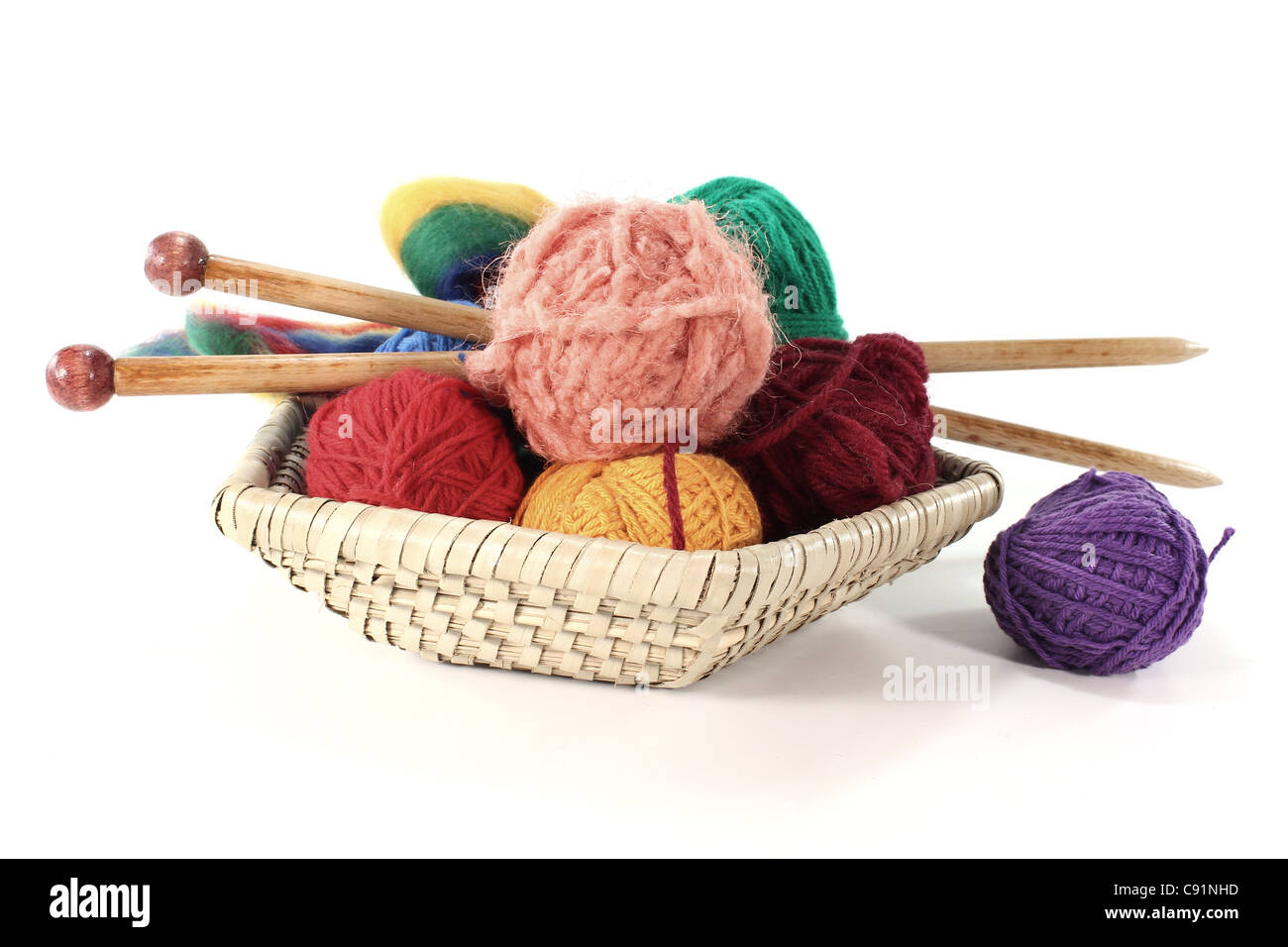 colorful ball of wool with knitting needles in a basket - Stock Image