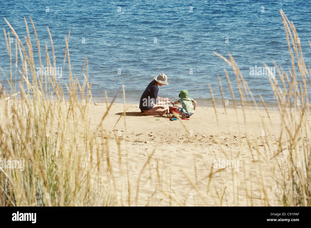 Mother and child playing on beach - Stock Image