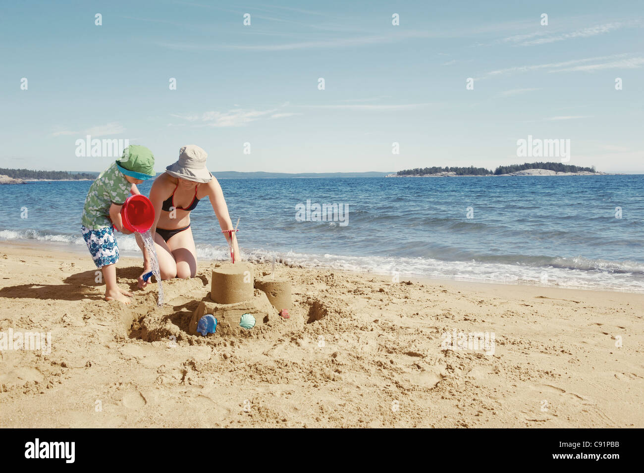 Mother and child building sandcastle - Stock Image