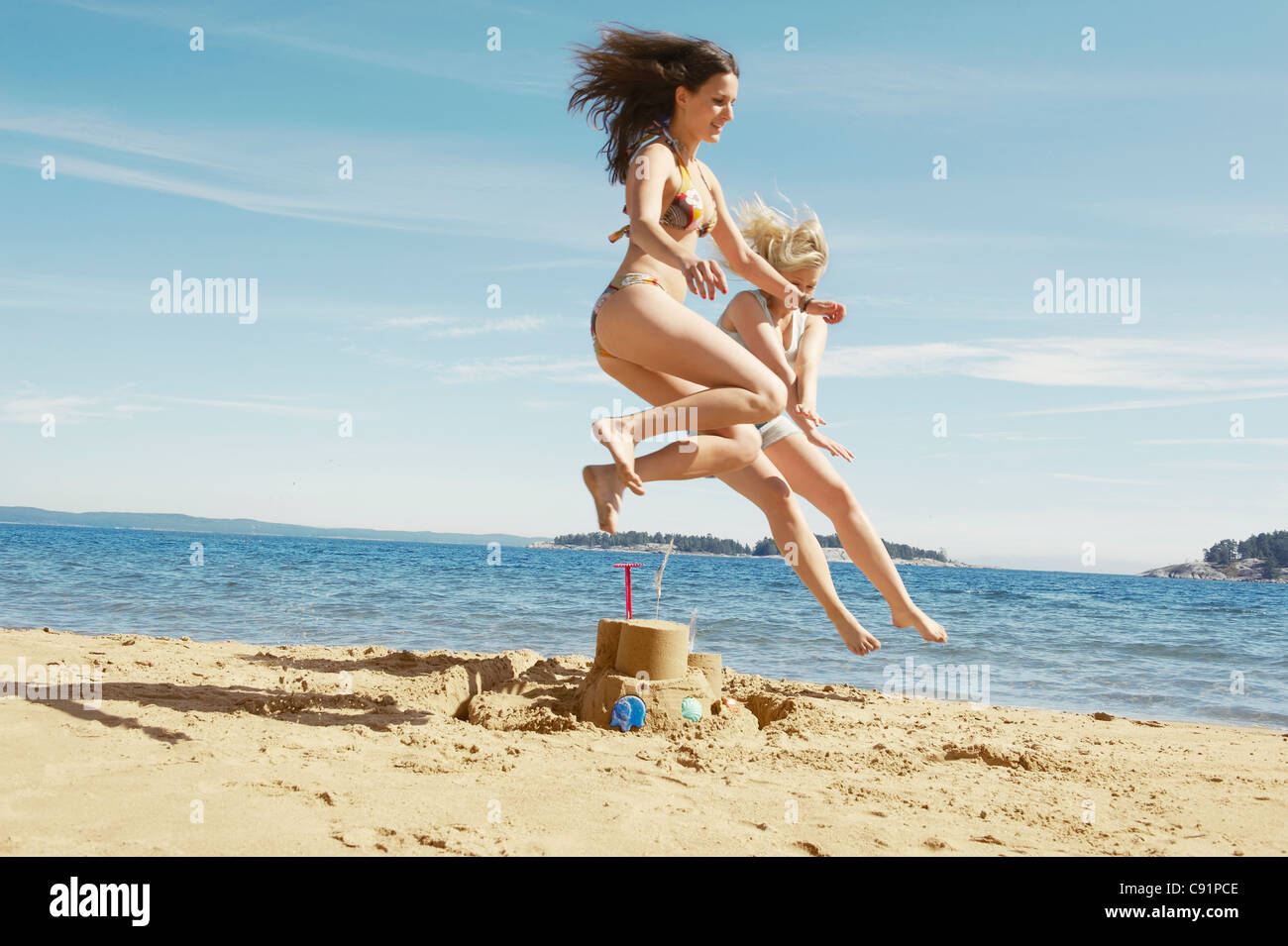 Women jumping over sandcastle - Stock Image
