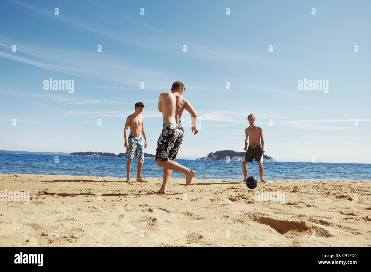 Men playing soccer on beach - Stock Image