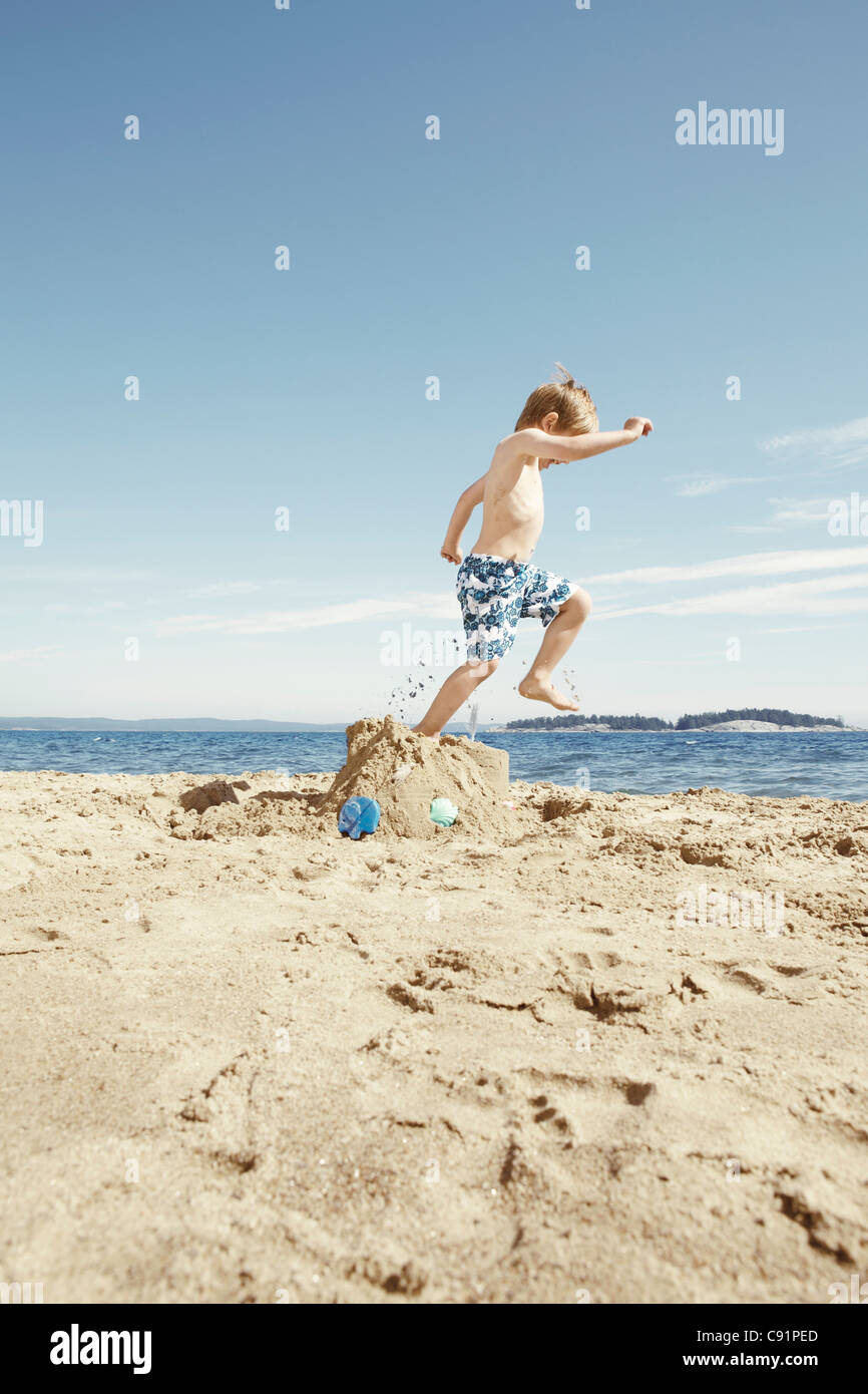 Boy stomping on sandcastle on beach - Stock Image