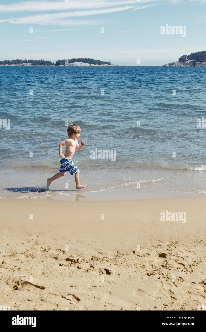 Boy running in waves on beach - Stock Image