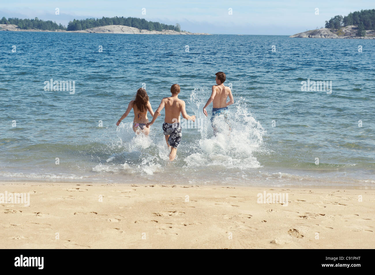Friends running into ocean on beach - Stock Image