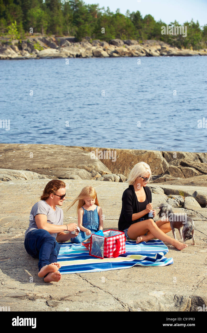 Family having picnic on rocks by lake - Stock Image