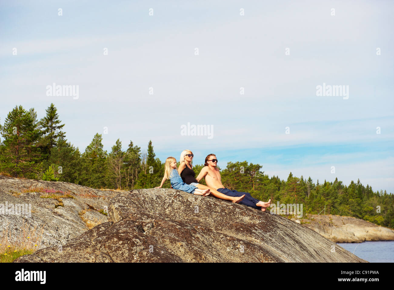 Family sitting on rock by lake - Stock Image