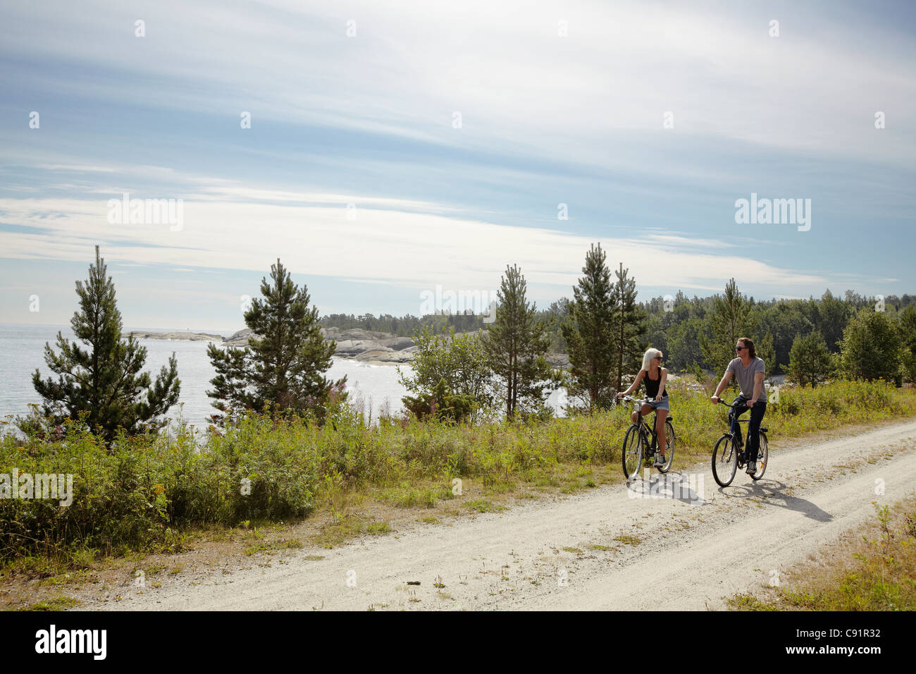 Couple bicycling on rural dirt path - Stock Image